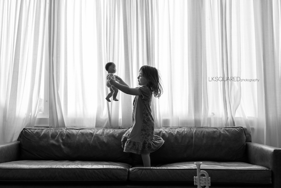 little girl dancing on the sofa with her babydoll